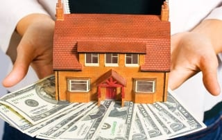 Person holds a miniature house and money
