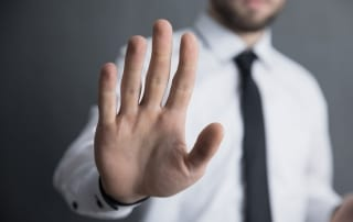 "businessman with hand raised in ""stop"" position"